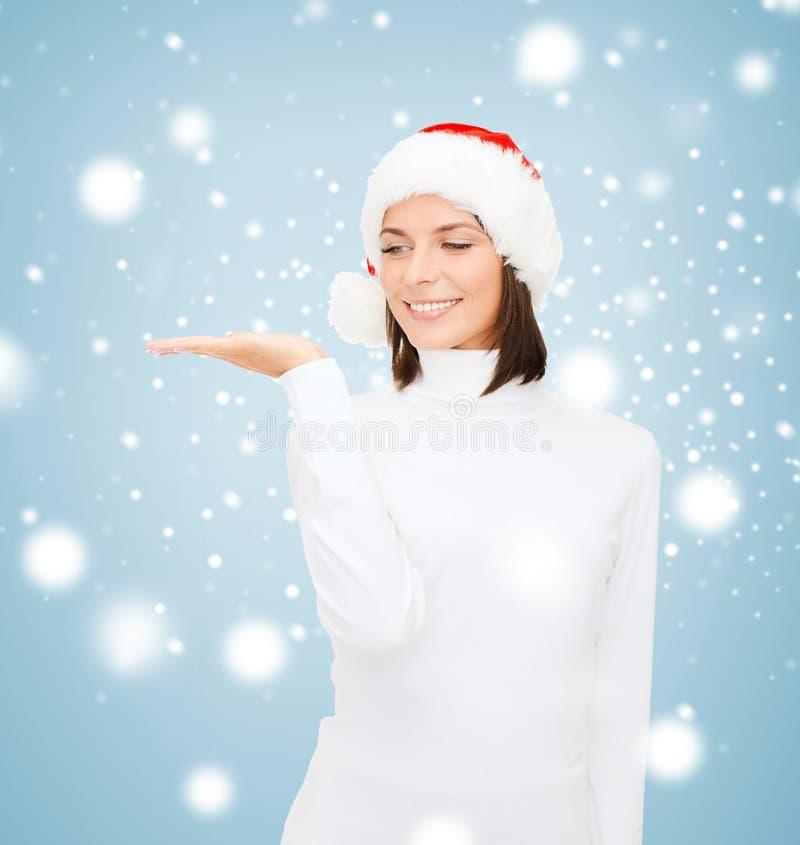 Mulher no chapéu do ajudante de Santa com algo na palma imagens de stock royalty free