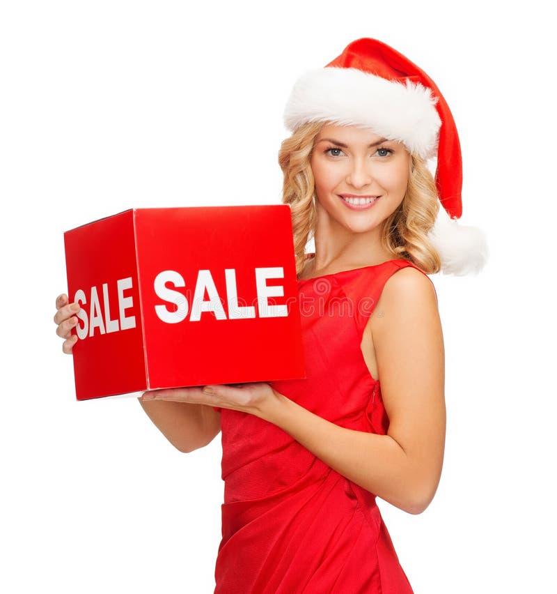 Mulher no chapéu do ajudante de Santa com sinal vermelho da venda fotografia de stock royalty free