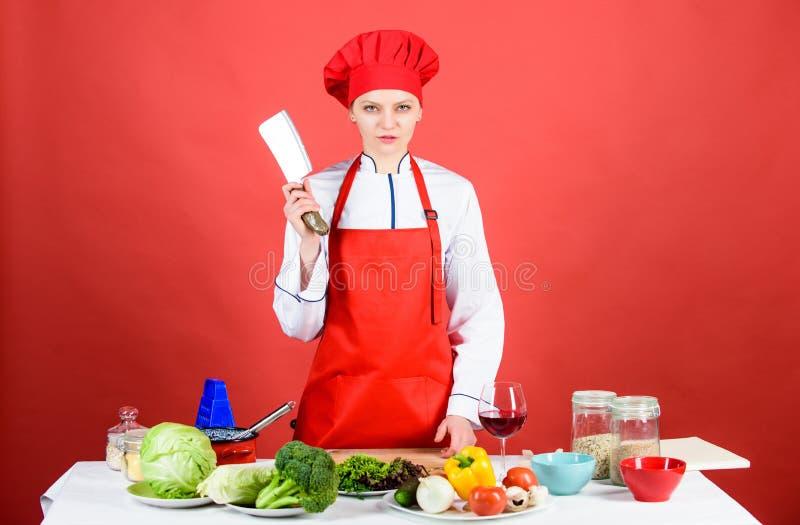 Mulher no chapéu do cozinheiro com faca O jantar de casamento com carne do rolo fumou e tomates dieting mulher séria que cozinha  fotos de stock royalty free