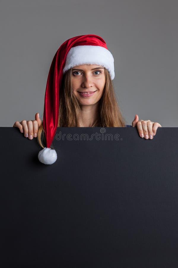 Mulher no chapéu do Natal de Santa que guarda o cartaz fotografia de stock royalty free