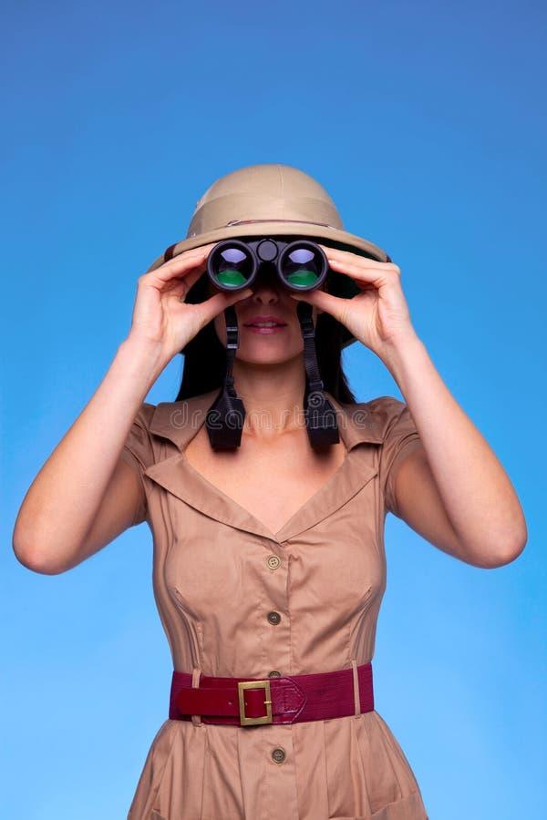Mulher no chapéu do safari que olha através dos binóculos imagens de stock royalty free
