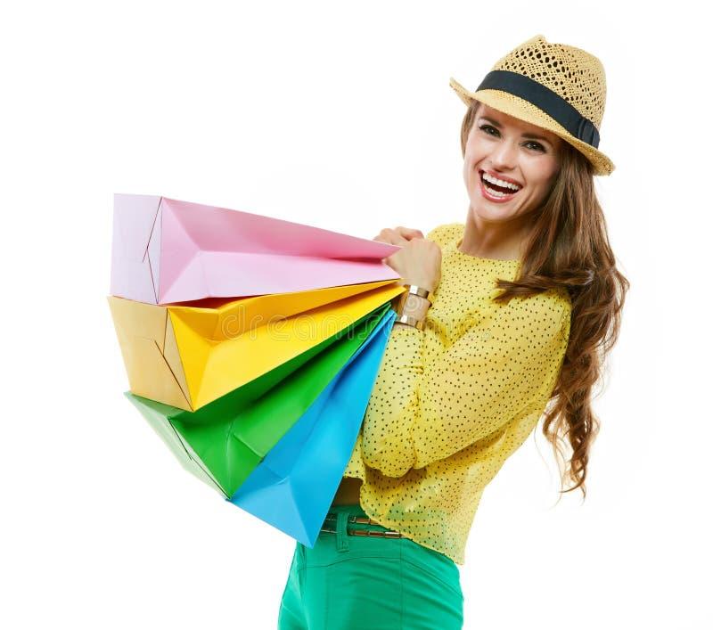 Mulher no chapéu e na roupa brilhante que guardam sacos de compras pesados foto de stock royalty free