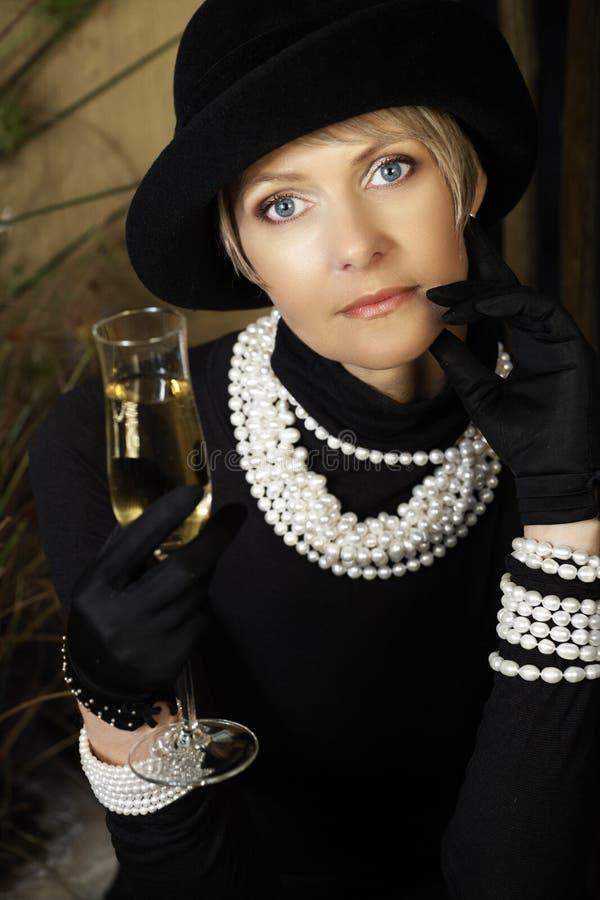 Mulher no chapéu, nas pérolas e no champanhe fotografia de stock
