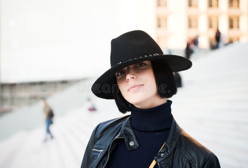 A mulher no chapéu negro e o revestimento levantam em escadas fotografia de stock
