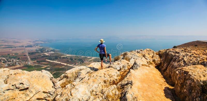 Mulher no chapéu que aprecia a vista panorâmica do mar de Galilee fotografia de stock royalty free