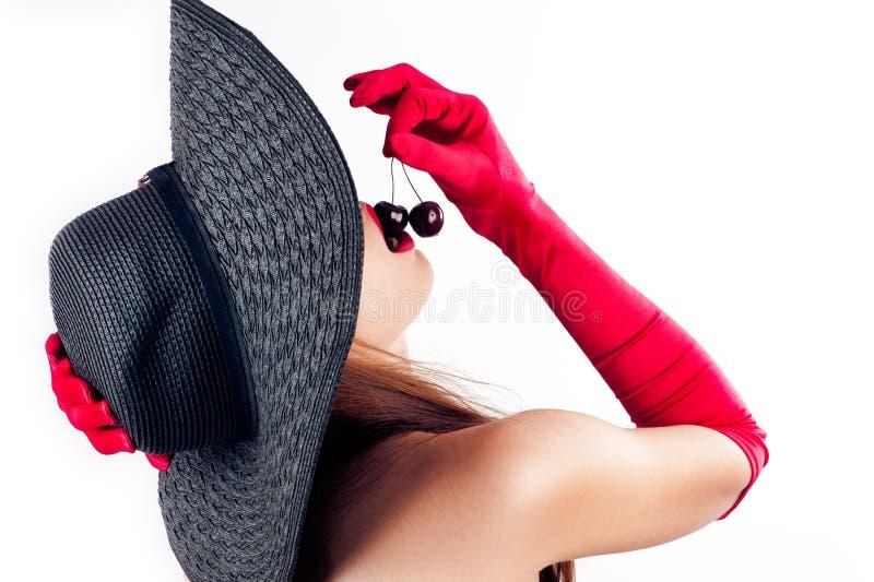 Mulher no chapéu que come duas cerejas foto de stock
