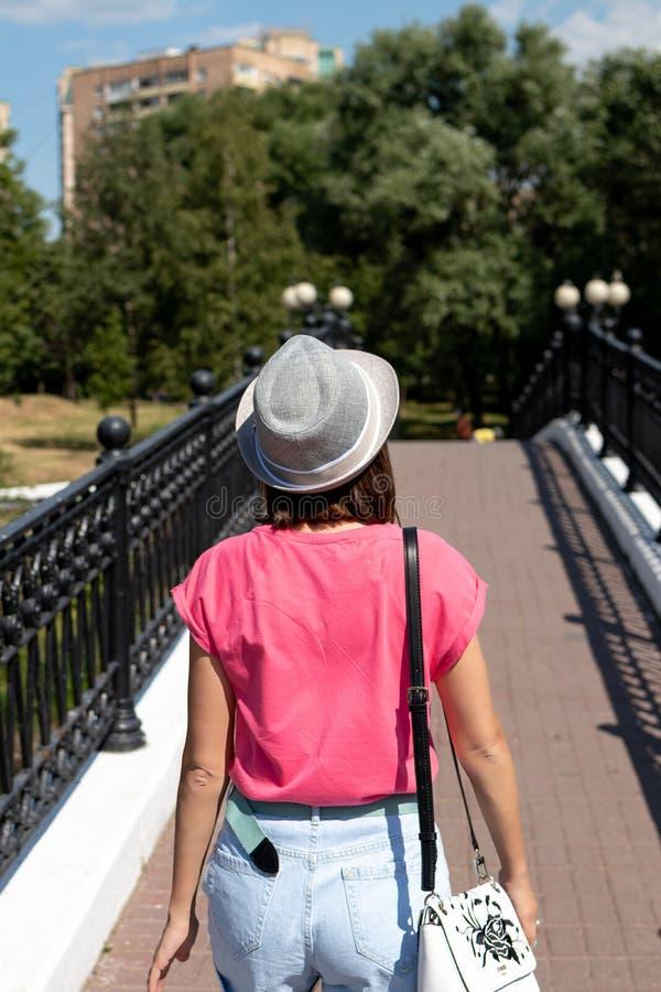Mulher no chapéu que levanta na ponte no parque da cidade foto de stock royalty free