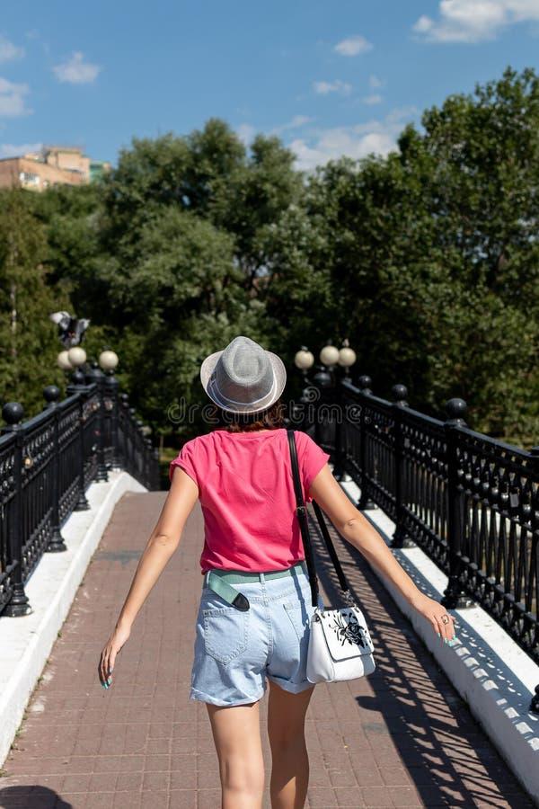 Mulher no chapéu que levanta na ponte no parque da cidade fotografia de stock royalty free