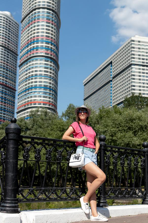 Mulher no chapéu que levanta na ponte no parque da cidade imagem de stock