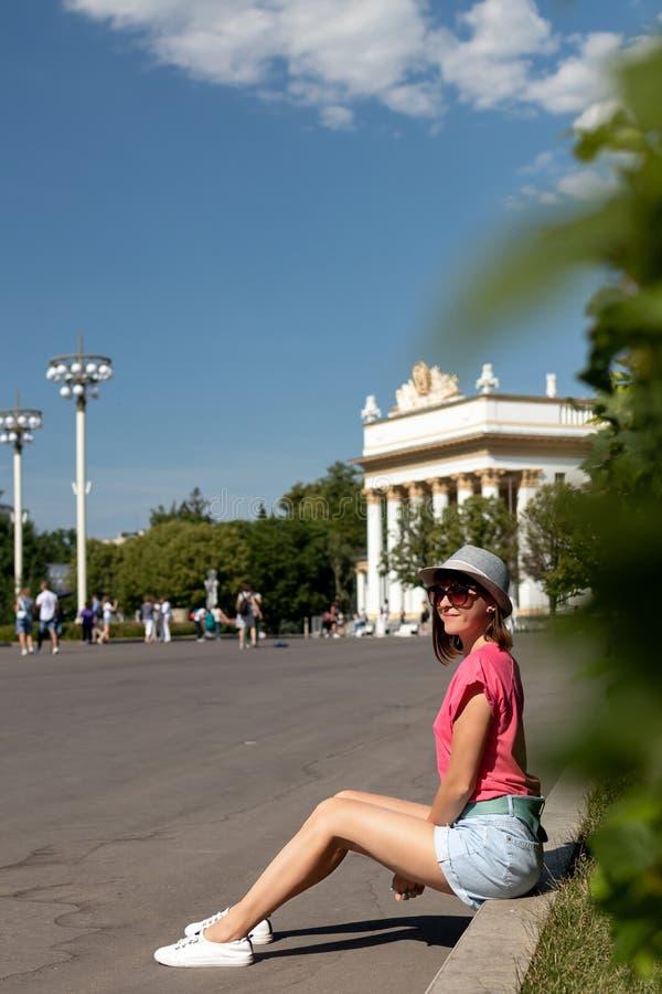 Mulher no chapéu que senta-se na beira no parque, Moscou imagens de stock royalty free