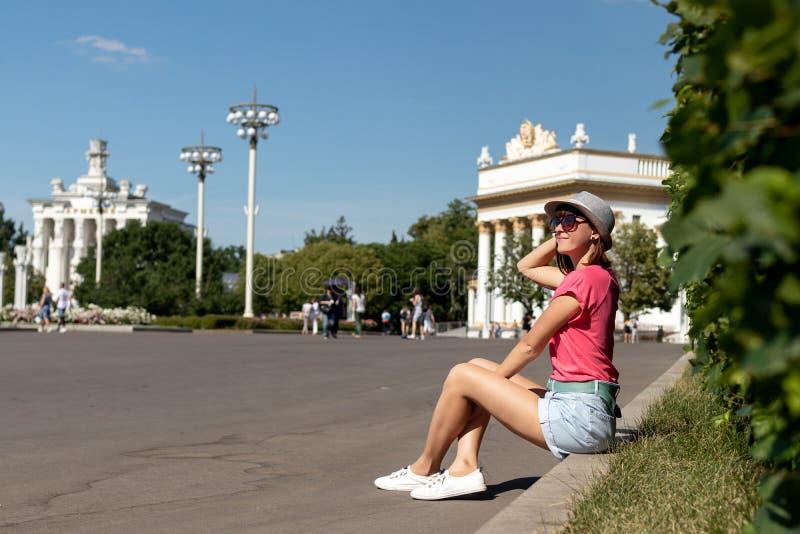 Mulher no chapéu que senta-se na beira no parque, Moscou fotos de stock royalty free