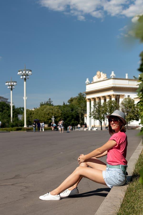 Mulher no chapéu que senta-se na beira no parque, Moscou fotografia de stock