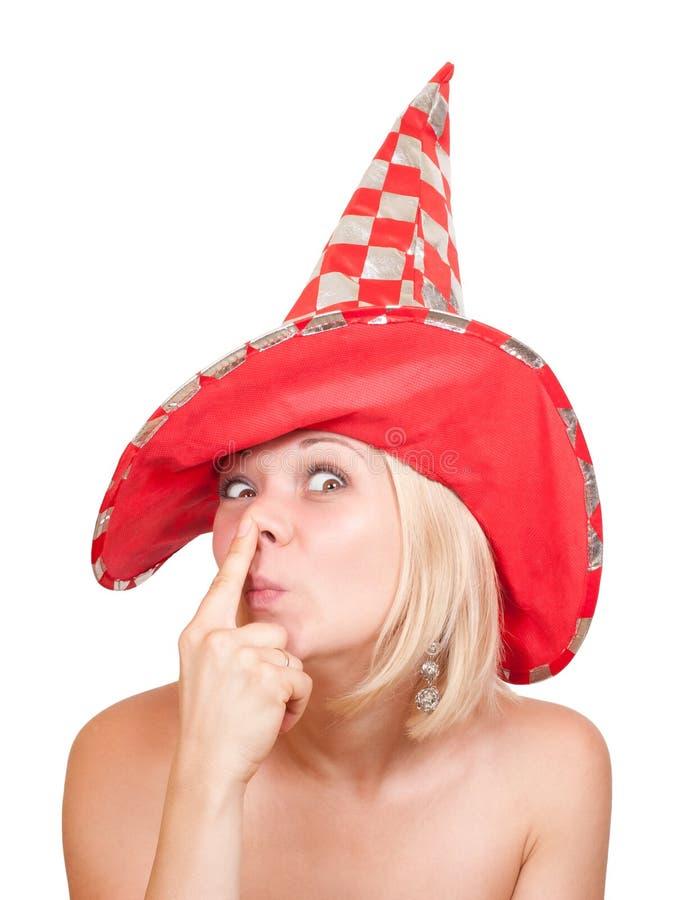 Mulher no chapéu vermelho que faz uma face engraçada no branco fotos de stock royalty free