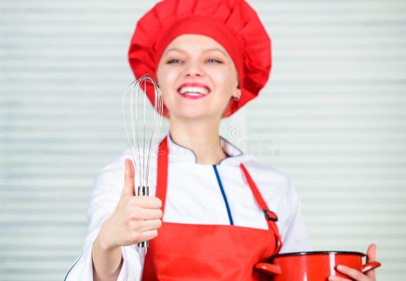 mulher no chap?u e no avental do cozinheiro mulher feliz que cozinha o alimento saud?vel pela receita Cozinheiro chefe profission fotos de stock