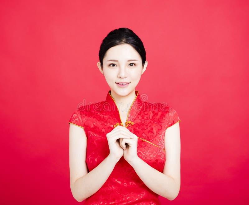 Mulher no cheongsam chinês com gesto das felicitações imagens de stock royalty free
