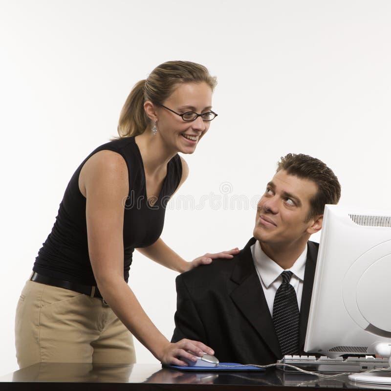 Mulher no computador com homem fotografia de stock royalty free