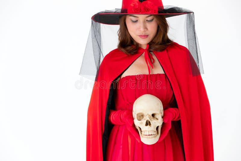 Mulher no crânio vermelho da terra arrendada do vestido no fundo branco Conceito FO foto de stock royalty free