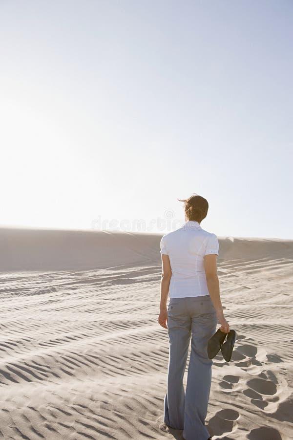 Mulher no deserto que guarda sapatas fotografia de stock royalty free