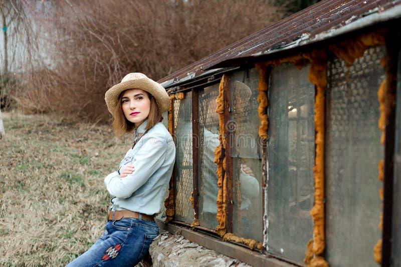 Mulher no desgaste ocidental no chapéu de vaqueiro, nas calças de brim e nas botas de vaqueiro fotos de stock royalty free