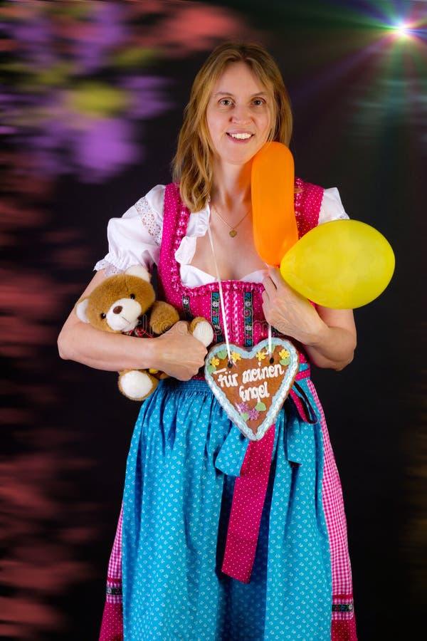 A mulher no dirndl ganhou alguns prêmios em Oktoberfest imagem de stock