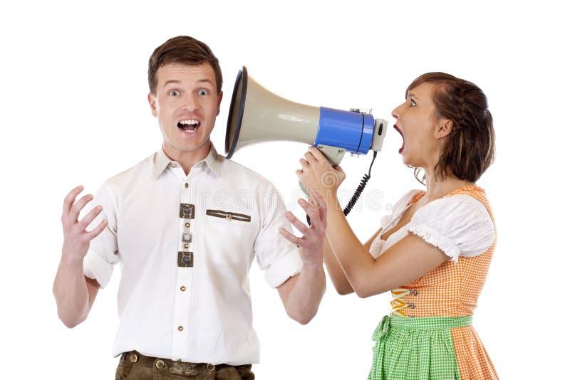 A mulher no dirndl grita para equipar no megafone fotografia de stock royalty free