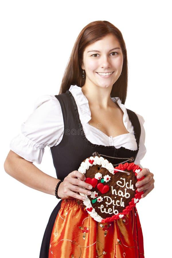 A mulher no Dirndl prende o coração do pão-de-espécie foto de stock royalty free