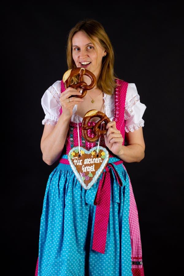 Mulher no dirndl que come o pretzel fotos de stock royalty free
