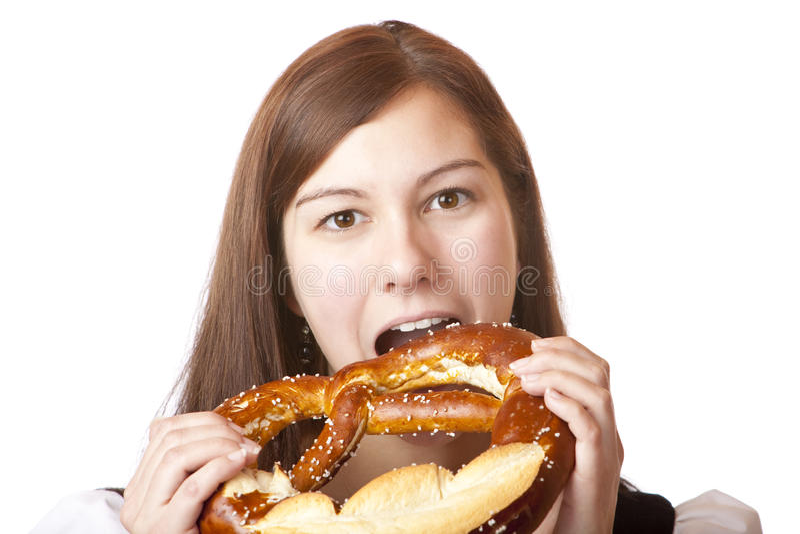 Mulher no Dirndl que come o pretzel de Oktoberfest fotos de stock