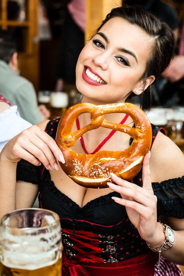 Mulher no Dirndl que come o pretzel de Oktoberfest fotografia de stock royalty free