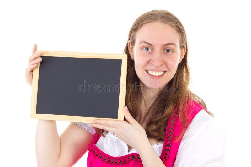 Mulher no dirndl que mostra o quadro-negro vazio foto de stock royalty free
