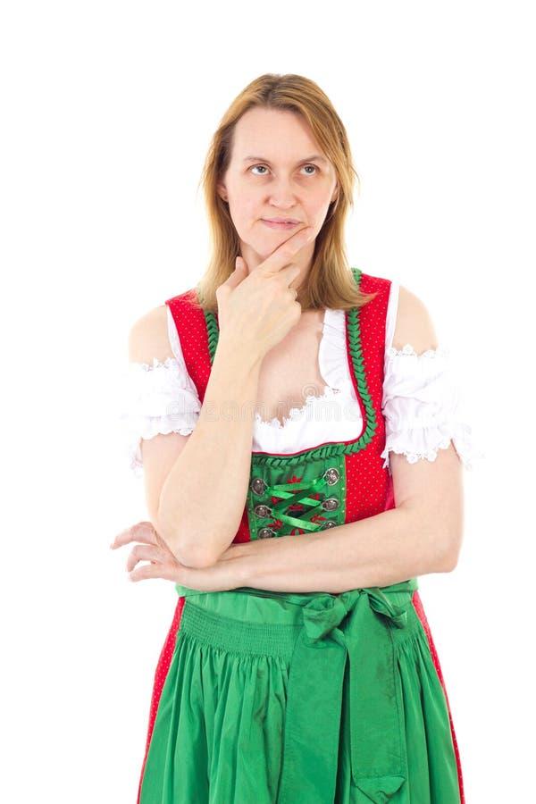 A mulher no dirndl verde vermelho está pensando fotografia de stock