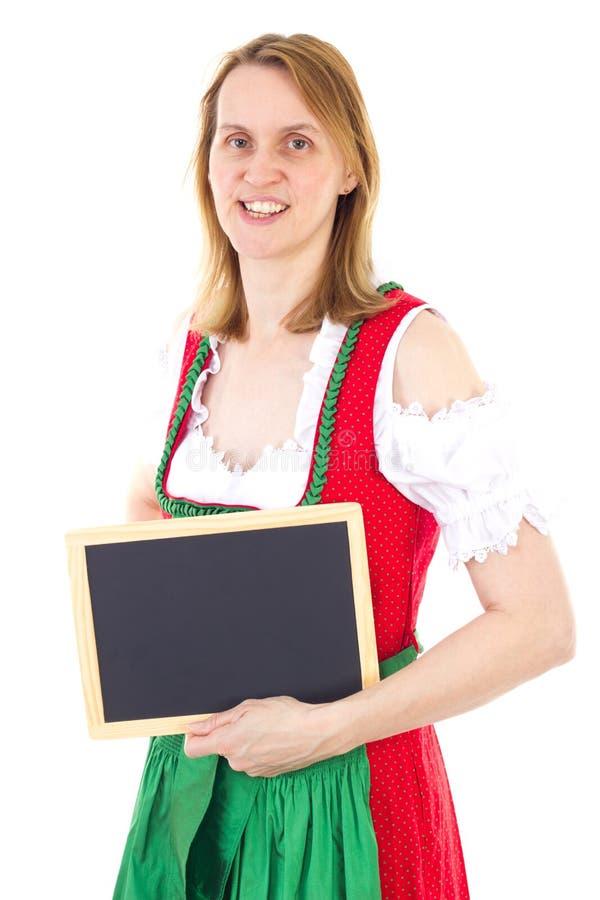 Mulher no dirndl verde vermelho que mostra o quadro-negro limpo imagem de stock
