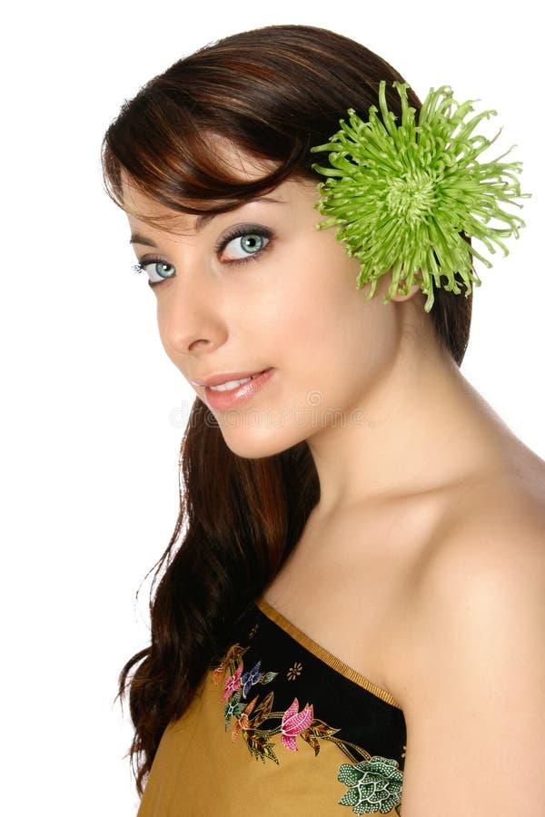 Mulher no envoltório do batik com o gerbera verde em seu cabelo imagens de stock