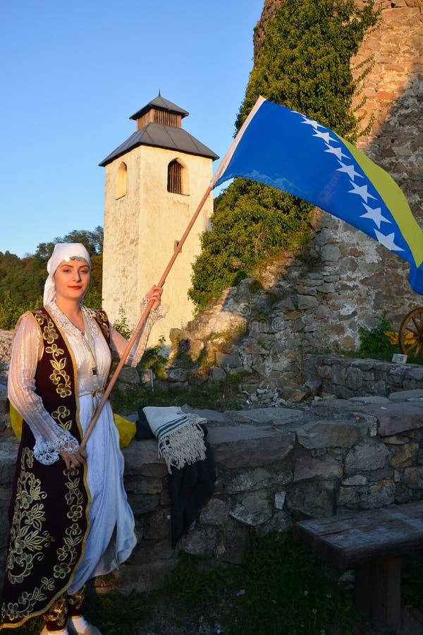 Mulher no equipamento bosniano tradicional com uma bandeira fotos de stock royalty free