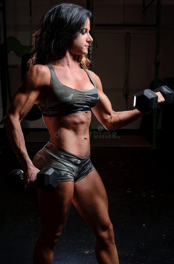 Mulher no equipamento da camuflagem que dá certo em um gym fotos de stock