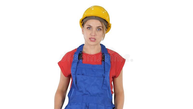 Mulher no equipamento da construção que fala à câmera ao andar no fundo branco imagens de stock royalty free