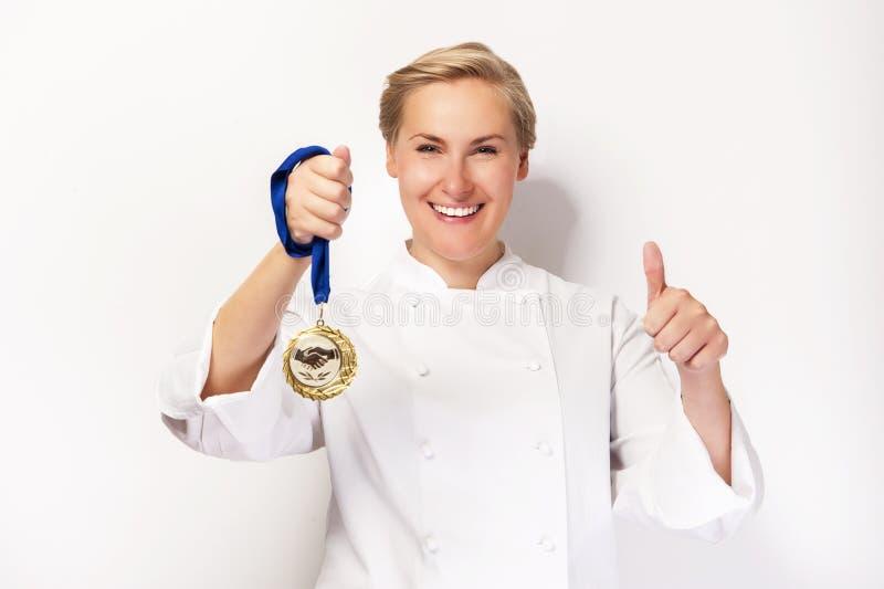 Mulher no equipamento do cozinheiro chefe com sorriso da medalha do prêmio ascendente e primeiro do polegar imagens de stock