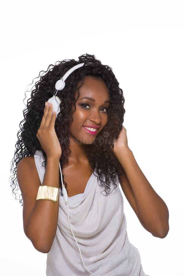 A mulher no equipamento ocasional escuta a música com fones de ouvido - isolado imagens de stock