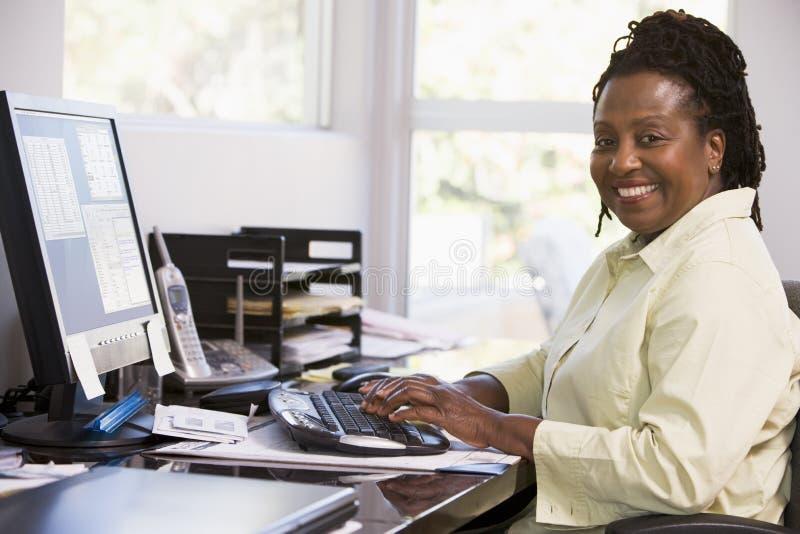 Mulher no escritório home usando o computador e o sorriso