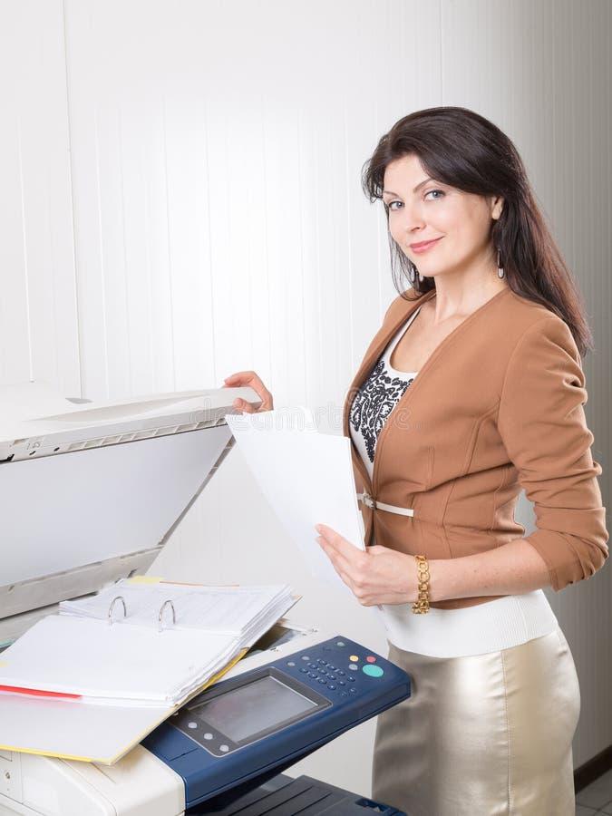 Mulher no escritório perto da copiadora com originais fotos de stock