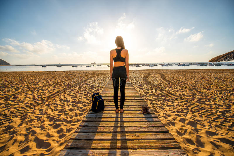 A mulher no esporte preto veste a posição na praia imagem de stock royalty free