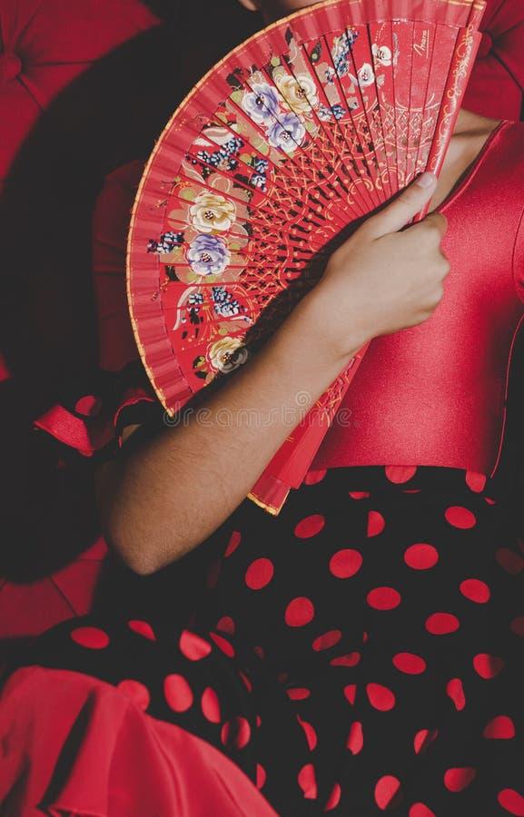 Mulher no fã vermelho da terra arrendada do vestido nas mãos fotografia de stock