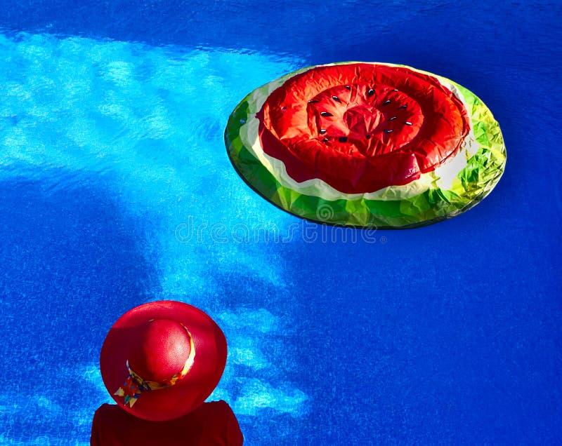 Mulher no flutuador da piscina e da melancia fotografia de stock