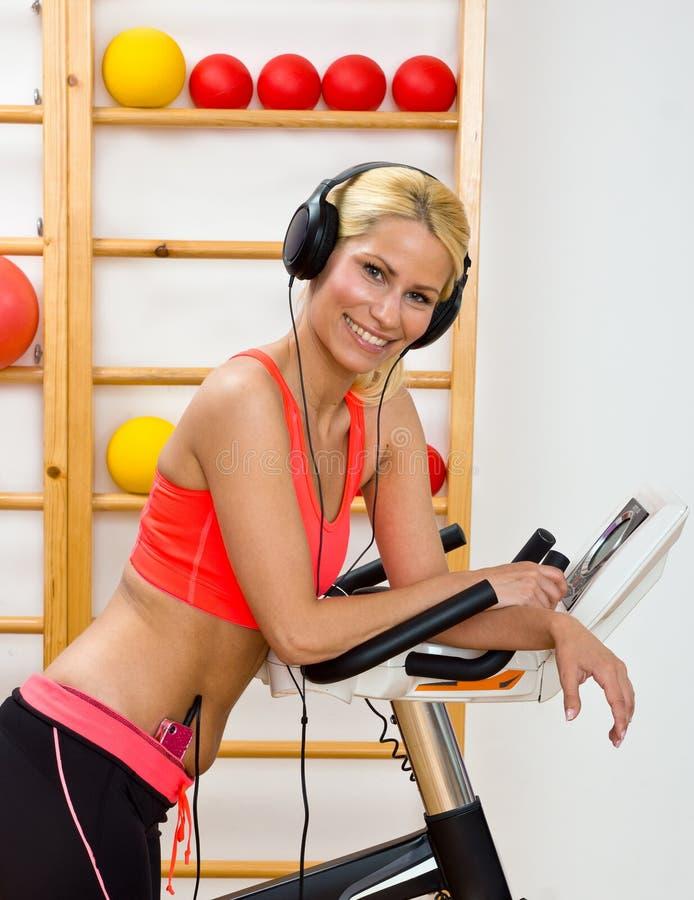 Mulher no gym com auscultadores imagens de stock