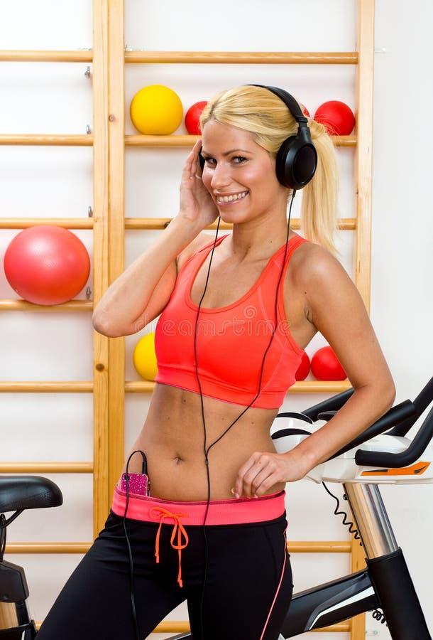 Mulher no gym com auscultadores imagem de stock