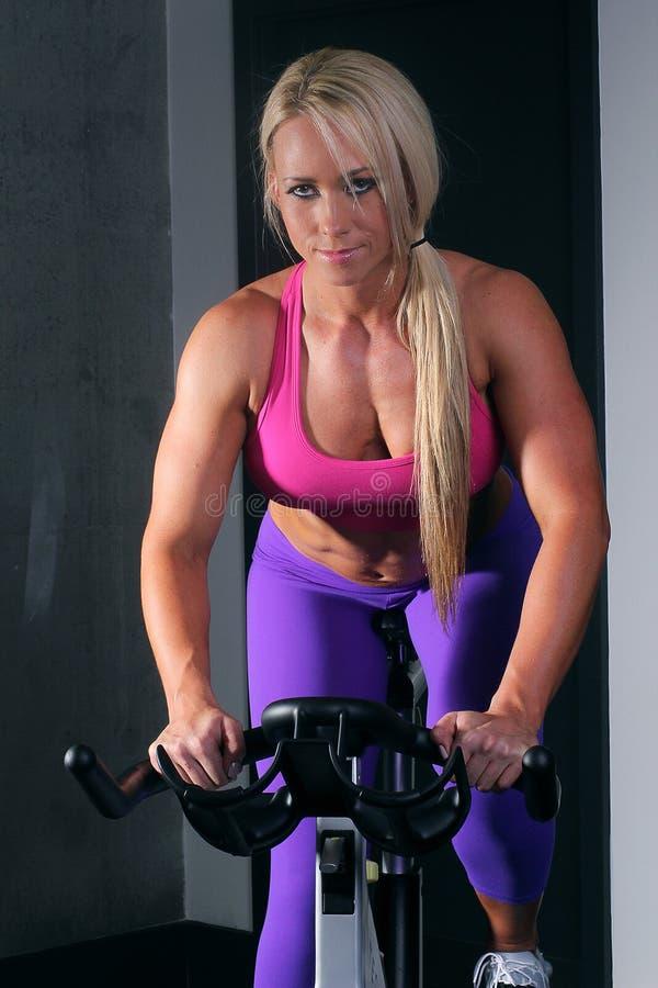 Mulher no gym em uma bicicleta imagem de stock