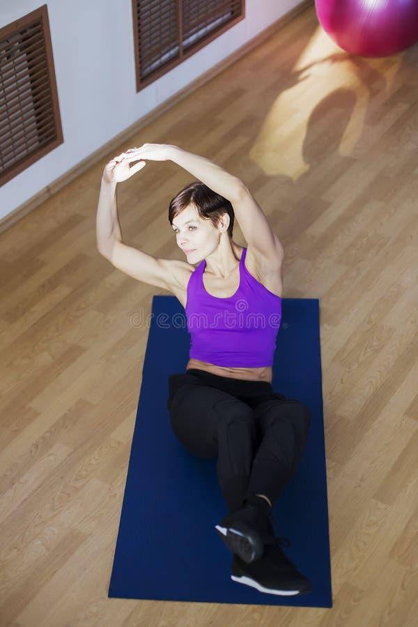 Mulher no gym que faz exercícios na esteira fotografia de stock royalty free