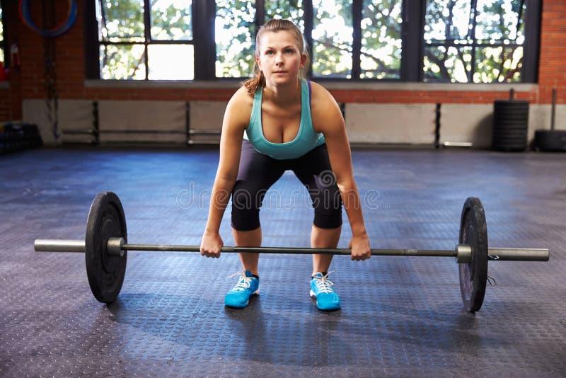 Mulher no Gym que prepara-se para levantar peso imagem de stock royalty free