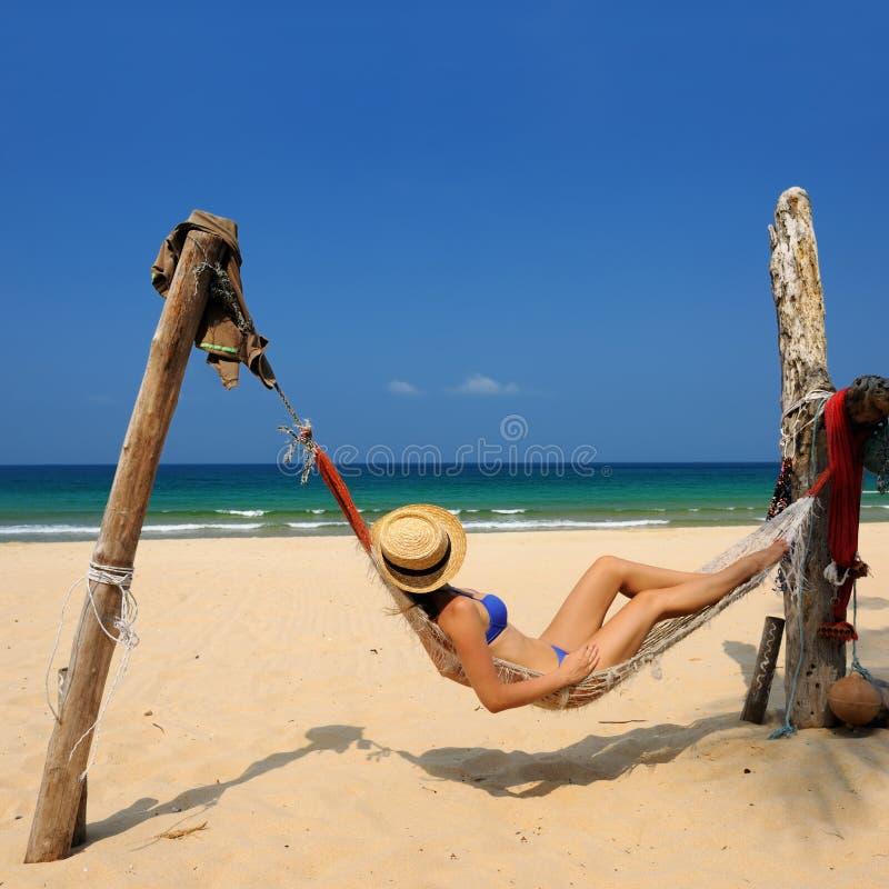Mulher no hammock na praia imagem de stock