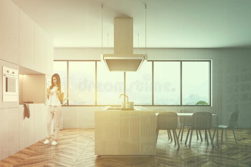 Mulher no interior branco da cozinha com uma tabela imagens de stock royalty free